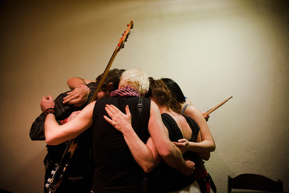 Kultur Shock gathers for their ritual pre-performance hug backstage at Gun Club in Belgrade, Serbia...