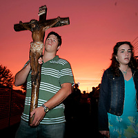 Seth Brown (L), of Clearwater, Florida. walks in a processional carrying a crucifix alongside supporters praying for Terri Schiavo during the final minutes of daylight outside the Woodside Hospice on March 23, 2005 in Pinellas Park, Florida. REUTERS/Scott Audette)