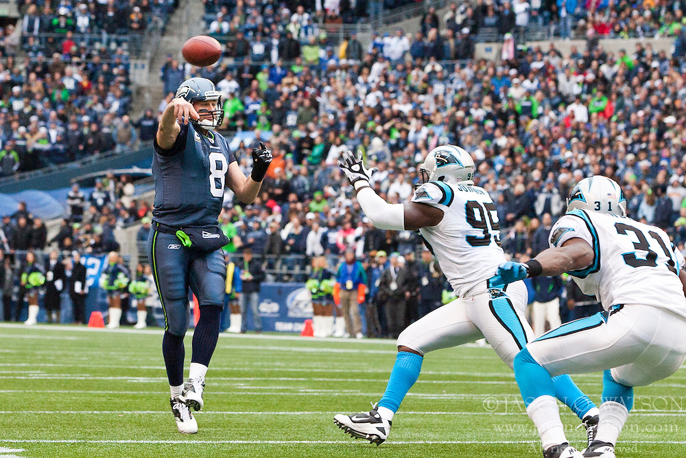December 5, 2010; Seattle, WA, USA;  Seattle Seahawks quarterback Matt Hasselbeck (8) throws a pass over Carolina Panthers defensive end Charles Johnson (95) and cornerback Richard Marshall (31)during the second quarter at Qwest Field. Seattle defeated Carolina 31-14.
