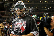 Washington Nationals outfielder Jayson Werth shakes beer and champagne out of his hair as he celebrates clinching a National League East Division championship on the field with his teammates .