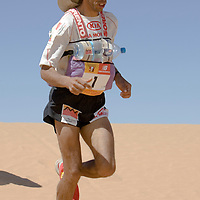 30 March 2007: Nine times winner of the men race #1 Lahcen Ahansal of Morocco runs over a dune in ergg Znaigui en route to check point 3 during fifth stage of the 22nd Marathon des Sables between west of Kfiroun and erg Chebbi (26.22 miles). The Marathon des Sables is a 6 days and 151 miles endurance race with food self sufficiency across the Sahara Desert in Morocco. Each participant must carry his, or her, own backpack containing food, sleeping gear and other material.