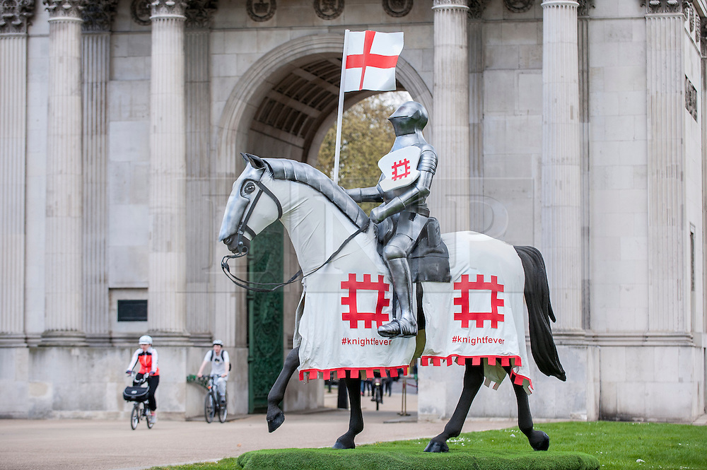 © Licensed to London News Pictures. 22/04/2015. Wellington Arch, London. Cyclists ride by as English Heritage unveil a 15ft St George at Wellington Arch in honour of the Patron Saint ahead of England's largest St George's Day celebration at Wrest Park as well as the launch of a nationwide tour which will see the knight open jousting tournaments at castles across England. Photo credit : Stephen Chung/LNP