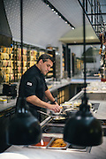 Chef Todd English preparing mini-burgers at Todd English Food Hall at the Plaza Hotel in New York City