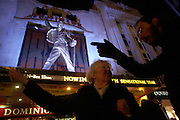 Lady visitor to London's Theatreland gets directions from a passer-by beneath a Freddy Mercury  outside the Dominion Theatre