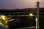 street light at dusk in a little village with above ground electric cables