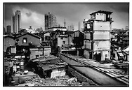Symbols of modernity rises behind hold outs in neighborhood doomed for destruction.  Families hold on to remains of their neighborhood as it is being demolished around them to make room for a new construction projects, probably a high rise building, Shanghai, China.