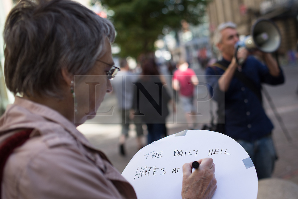 "© Licensed to London News Pictures . 06/10/2013 . Manchester , UK . A woman writes "" The Daily Heil hates me"" on a placard . A demonstration against the Daily Mail newspaper in central Manchester's St Anne's Square today (6th October 2013) . Photo credit : Joel Goodman/LNP"