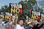 """People shout slogans and hold up placards which read """"The Abe Administration - No"""" during a rally against Japanese Prime Minister Shinzo Abe in Tokyo on March 22, 2015. Several thousand people took part in the rally to denounce fascism and protest against Abe's administration."""