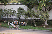 Two men and a bike roadside. Wenzhou, China.