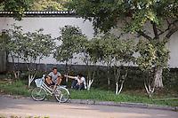 Two men and a bike roadside. Wenzhou, China.