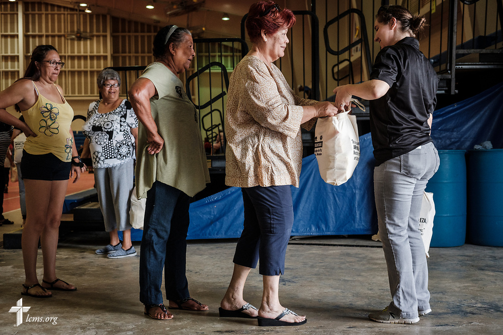 Teacher Ruth Maita distributes bags of food and supplies from Iglesia Luterana Principe de Paz (Prince of Peace Lutheran Church), Mayagüez, Puerto Rico, and flowing from its mercy arm, Casa de Amparo y Respuesta a Desastre (CARD), or House of Refuge and Mercy Response mercy center, with funding by LCMS Disaster Response, to residents at a food distribution event in a local community center on Tuesday, April 17, 2018 in Mayagüez. LCMS Communications/Erik M. Lunsford