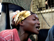 A woman sings to relieve herself and her travel companions after a long bus trip from Changugu to Kibuye along the Kivu banks.