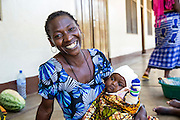 Fatuma Nandaga and her baby niece Rukia sit in the shade and cool air outside the children's ward of St Walburg's Hospital, Nyangao. Lindi Region, Tanzania.