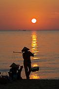 Phu Quoc Island. Long Beach (Bai Truong). Women with cone hats at sunset.