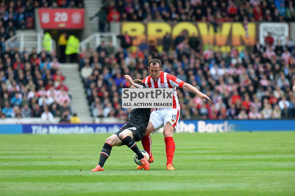 Charlie Adam of Stoke tackles Liverpool player Alberto Moreno