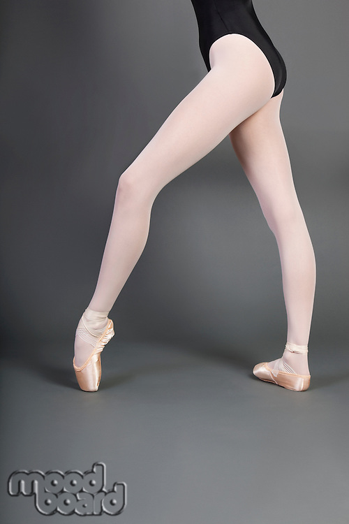 Low section of young ballet dancer wearing ballet slippers over grey background