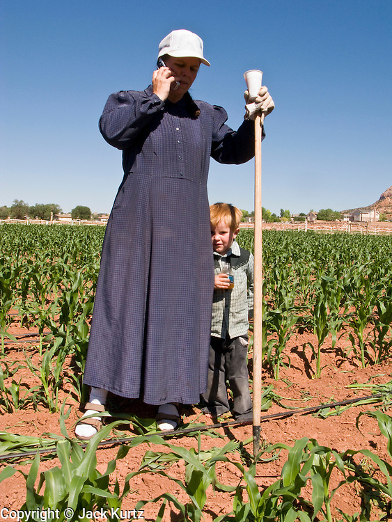 "June 16, 2008 -- COLORADO CITY, AZ: A member of the Jessop family makes a cell phone call while weeding the community corn plot in Colorado City, AZ. The Jessops are a polygamous family and members of the FLDS. Colorado City and neighboring town of Hildale, UT, are home to the Fundamentalist Church of Jesus Christ of Latter Day Saints (FLDS) which split from the mainstream Church of Jesus Christ of Latter Day Saints (Mormons) after the Mormons banned plural marriage (polygamy) in 1890 so that Utah could gain statehood into the United States. The FLDS Prophet (leader), Warren Jeffs, has been convicted in Utah of ""rape as an accomplice"" for arranging the marriage of teenage girl to her cousin and is currently on trial for similar, those less serious, charges in Arizona. After Texas child protection authorities raided the Yearning for Zion Ranch, (the FLDS compound in Eldorado, TX) many members of the FLDS community in Colorado City/Hildale fear either Arizona or Utah authorities could raid their homes in the same way. Older members of the community still remember the Short Creek Raid of 1953 when Arizona authorities using National Guard troops, raided the community, arresting the men and placing women and children in ""protective"" custody. After two years in foster care, the women and children returned to their homes. After the raid, the FLDS Church eliminated any connection to the ""Short Creek raid"" by renaming their town Colorado City in Arizona and Hildale in Utah. The Jessops are a polygamous family and members of the FLDS.     Photo by Jack Kurtz"