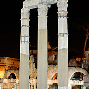 Tall columns of the Roman ruins of the Foro Romano in Rome, Italy, at night.