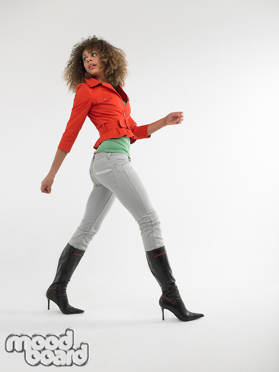 Woman with curly hair walking  in studio