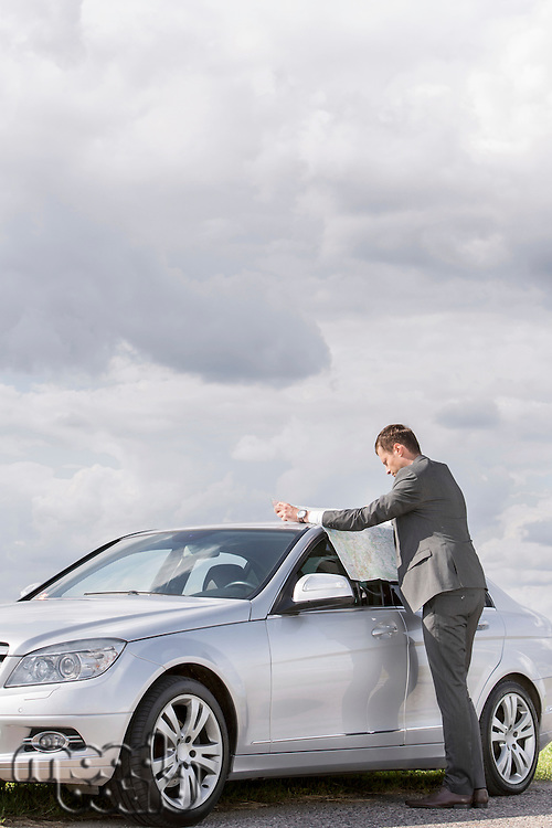 Full length side view of businessman reading map by car at countryside