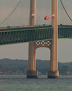 A Coast Guard helicopter searches the waters of the Straits of Mackinac for a woman who either fell or jumped from the bridge.