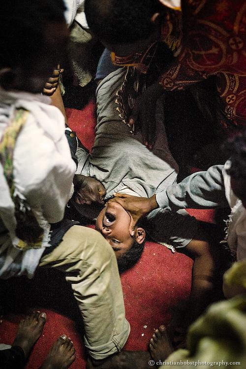 Ein Geistlicher führt einen Exorzismus an einer jungen Frau durch, welche nach der Berührung durch das Kreuz von fünf Personen festgehalten werden muss.