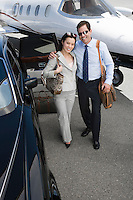 Businesswoman and businessman standing in front of airplane and embracing, elevated view.