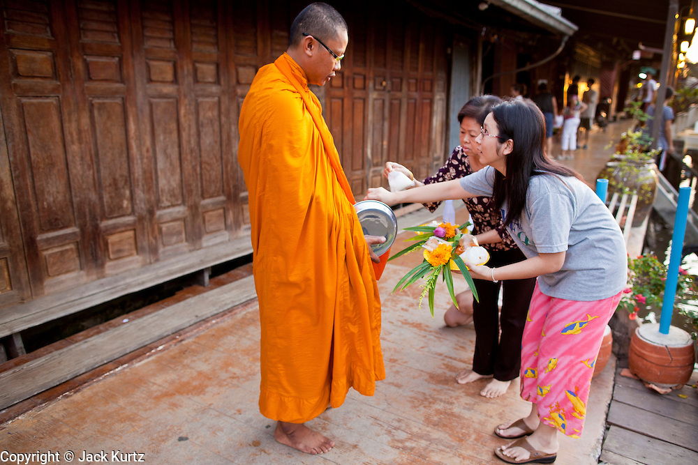 "10 JULY 2011 - AMPHAWA, SAMUT SONGKRAM, THAILAND:   Thai women present a monk with an offering during his morning alms rounds in Amphawa, Thailand, about 90 minutes south of Bangkok. The Thai countryside south of Bangkok is crisscrossed with canals, some large enough to accommodate small commercial boats and small barges, some barely large enough for a small canoe. People who live near the canals use them for everything from domestic water to transportation and fishing. Some, like the canals in Amphawa and nearby Damnoensaduak (also spelled Damnoen Saduak) are also relatively famous for their ""floating markets"" where vendors set up their canoes and boats as floating shops.      PHOTO BY JACK KURTZ"