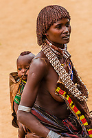 Hamer woman carrying baby on her back, Hamer tribe weekly market in Turmi, Omo Valley, Ethiopia.