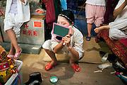 Chaozhou style opera in Shek Tong Tsui district, Hong Kong. Back stage make up