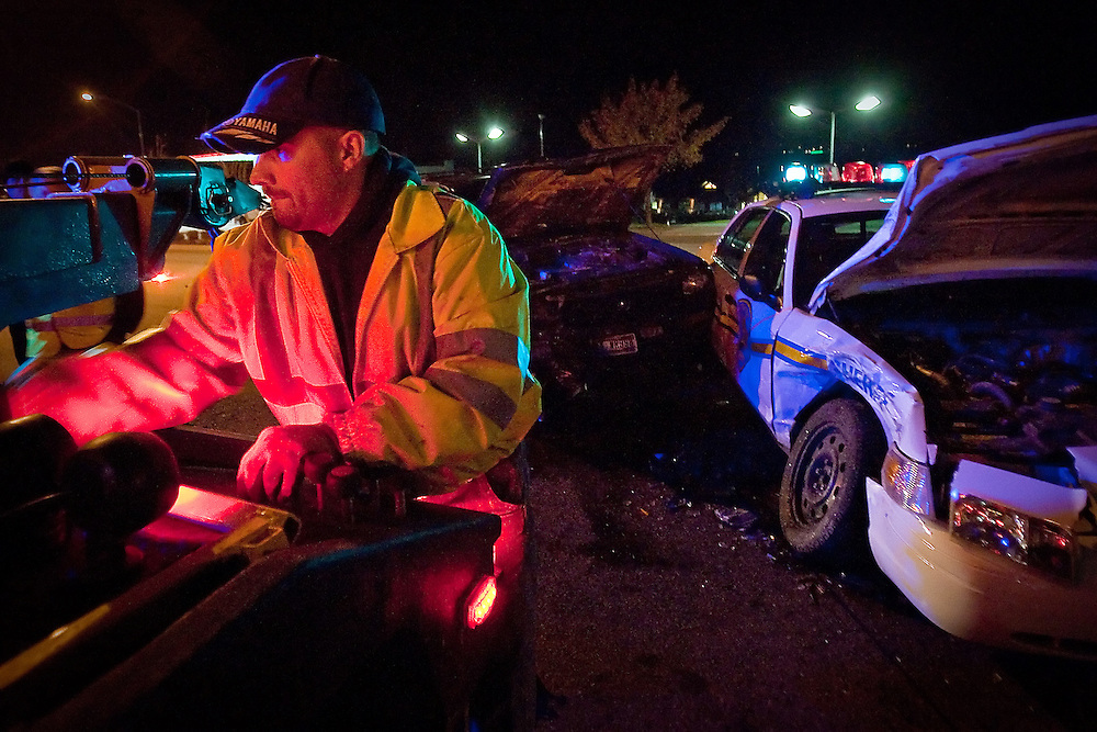 JEROME A. POLLOS/Press..Phil Rohr, with Rohr Towing, prepares to two away an sport utility vehicle that collided with a Kootenai County Sheriff deputy's patrol car Monday on Northwest Blvd. The deputy received minor injuries in the accident. Idaho State Police is investigating the accident.