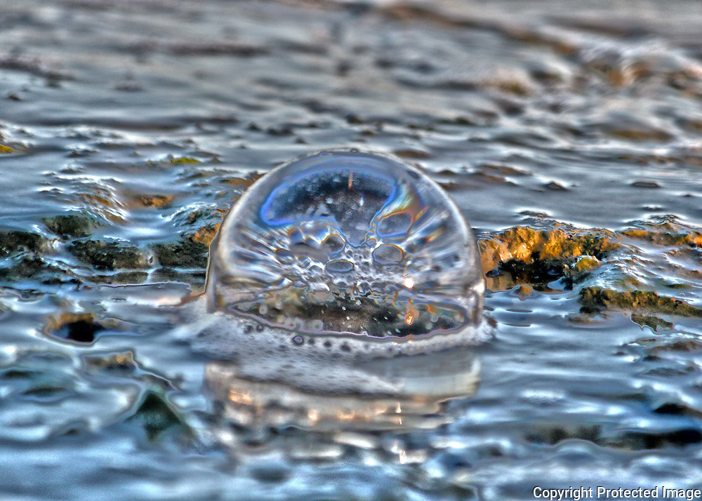 Crystal ball in a tidal pool on a Jekyll Island beach reflecting surf bubbles.