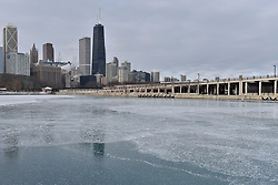 © Licensed to London News Pictures. 31/12/2017. CHICAGO, USA.  The John Hancock Center skyscrapers is reflected in ice as the waters of Lake Michigan around Chicago have frozen during a period of sub-zero temperatures.  Extremely cold conditions are forecast to continue into the New Year. Photo credit: Stephen Chung/LNP