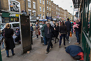 A homeless man sleeps in Brick Lane through an impromptu gig by indie band Third Party Incidents with Tom Henry (guitar) visible on the first floor on the left  ( and Stef Hale (drums) not visible), East End, London.