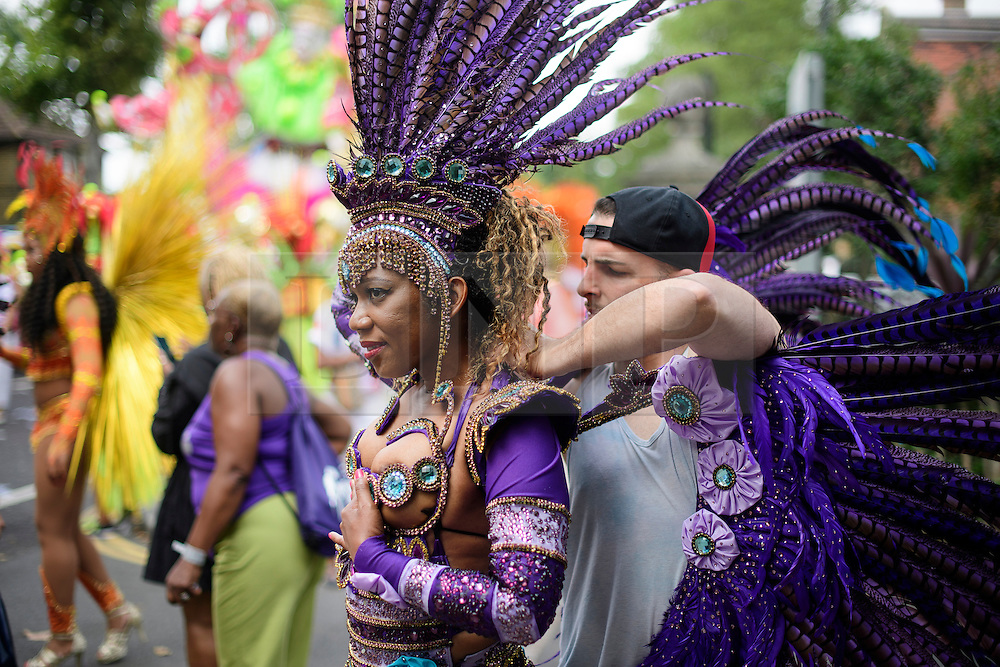 © Licensed to London News Pictures. 29/08/2016. London, UK. A carnival goer has her costume adjusted before taking part in day two of the Notting Hill carnival, the second largest street festival in the world after the Rio Carnival in Brazil, attracting over 1 million people to the streets of West London.  Photo credit: Ben Cawthra/LNP