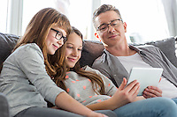 Father and daughters using tablet PC on sofa at home
