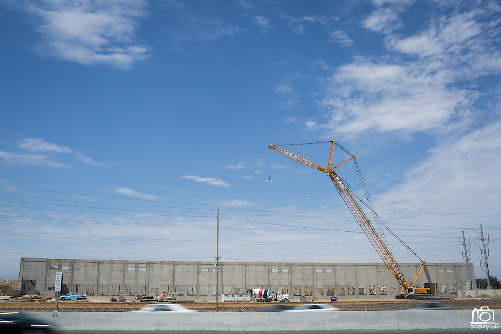A crane towers over one of three large pop-up buildings at the Dixon Landing Road exit of I-880, which is planned to be a shopping center named The Crossings @880, in Milpitas, California, on July 15, 2014. (Stan Olszewski/SOSKIphoto)