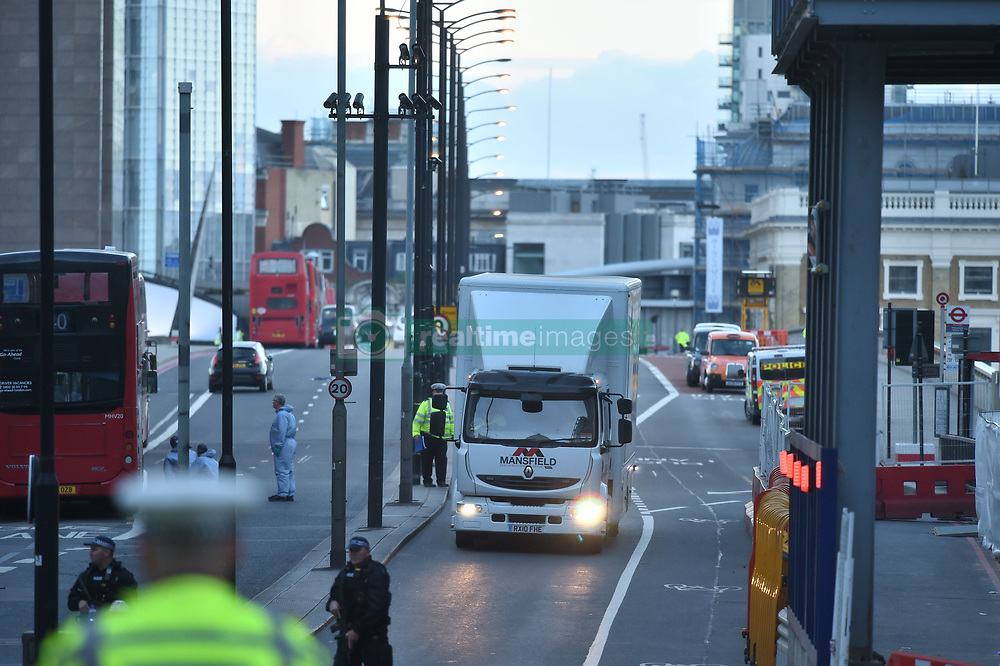 The van used in the attack is removed from the scene inside a lorry on the north side of London Bridge following last night's terrorist incident.
