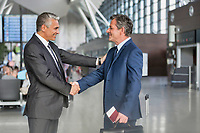 Mature businessman shaking hands with business partner in airport