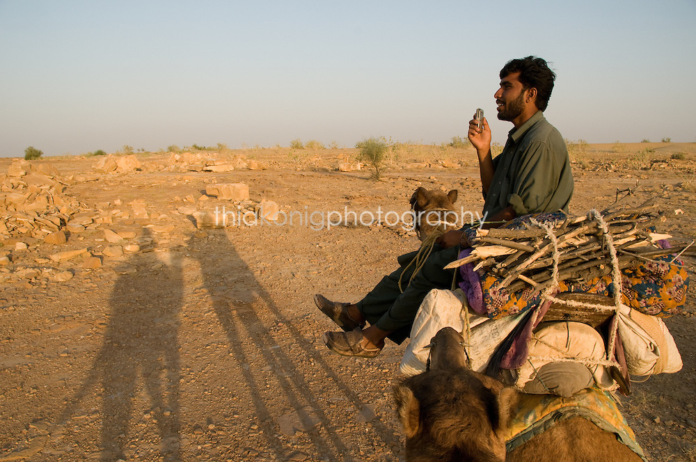 Muslim camel driver talking on his cell phone, outskirts of Jaiselmer, India