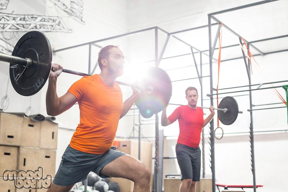 Men lifting barbells in crossfit gym