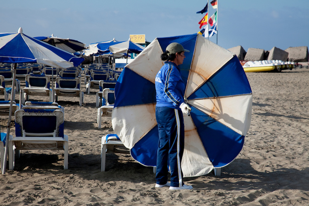 Setting up the umbrellas early in the morning on the beach in Los Cristianos, South Tenerife.