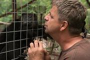 Paul Walker of Wildtracks and black howler monkey (Alouatta pigra)<br /> Primate Rehabilitation Center<br /> Sarteneja<br /> Belize,<br /> Central America