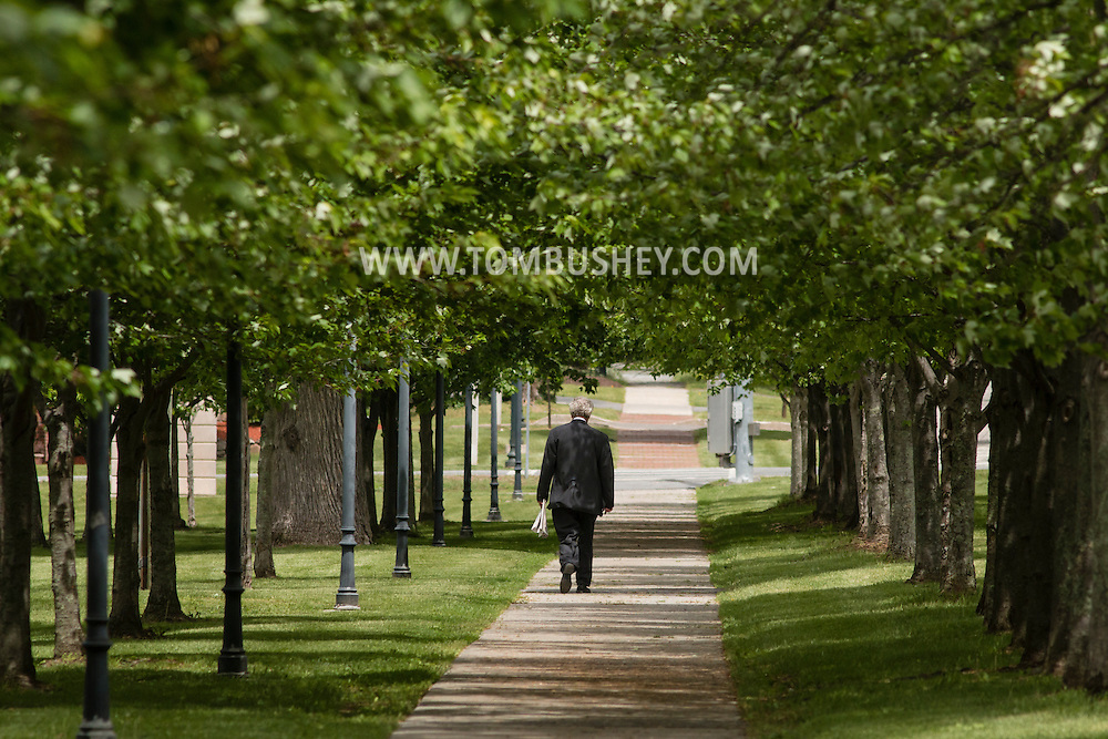 Goshen, New York - A man walks through a tunnel of trees in front of the Orange County Government Center and Courthouse on May 20, 2015.