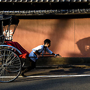 A tour guide pulls passengers in a rickshaw in Gion, a popular art and entertainment district in Kyoto, Japan.