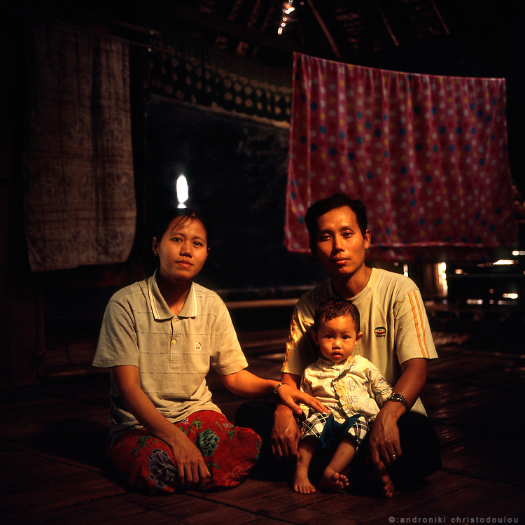 "Karen couple: Ler Lay Kler (32) with his wife Shirley (29) and their child Cherry (14 months old), inside their house at Mae La refugee camp. Ler Lay comes from Mon state in Burma and has been to the camp since 1993. Shirley has been at the camp since 2005. They met and got married in the camp. .Burmese refugee camp ""Mae La"" is north of border-town Mae Sot and lies along the Thai-Burmese border on the side of Thailand. Approximately 50,000 people live there. 38,167 was the official number of registered people in November 2009, according to the Thailand Burma Border Consortium (TBBC), and the rest are unregistered or people who come and go."