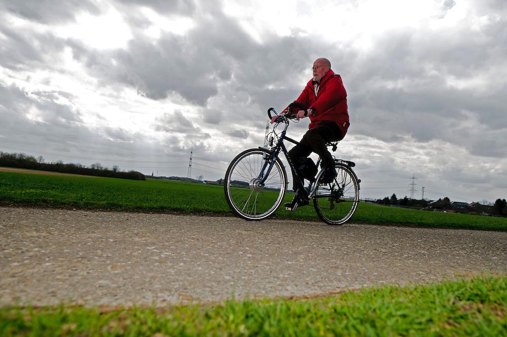 Deutschland , Ein Rentner auf einem Elektrofahrrad auf einem Feldweg  |  Germany, a man on an e-bike  is riding along on a rural road |