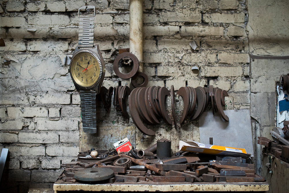 A large novelty watch hangs above a work bench at Azov Engineering Group's garage on September 9, 2015 in Kyiv, Ukraine.