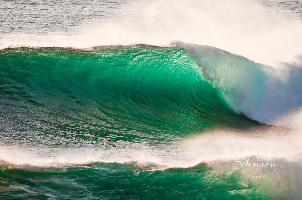 Powerful backlit wave breaking off rocky coast, Hawaii
