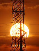 A tower from Salt Lake City, Utah's power grid is silhouetted by the setting sun, April 16, 2008. With oil prices rising, many are looking to get off the grid by using solar power.  Braley/Stock
